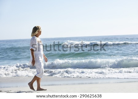 Senior Woman Walking along Sandy Beach