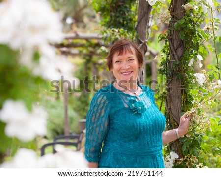 Senior woman  walking in  park with blooming roses - stock photo