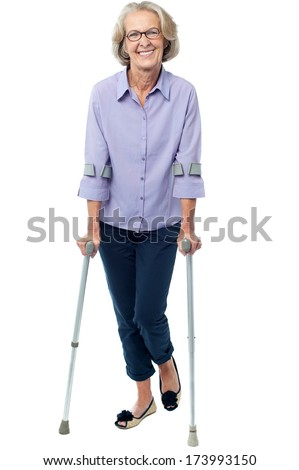 Senior woman walking with the help of crutches