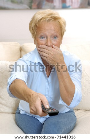 Senior woman watching tv and holding a remote control. Shocked senior woman holding a remote control.