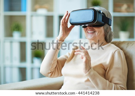 Senior woman watching video via vr glasses