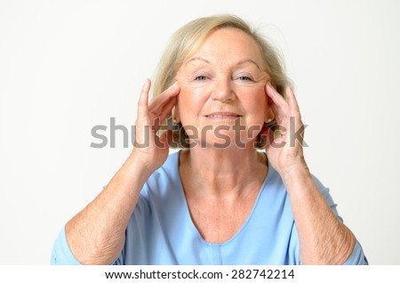 Senior woman wearing blue shirt while showing her face, effect of aging caused by loss of elasticity, close-up - stock photo