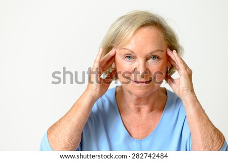 Senior woman wearing blue shirt while showing her face, effect of aging caused by loss of elasticity, close-up