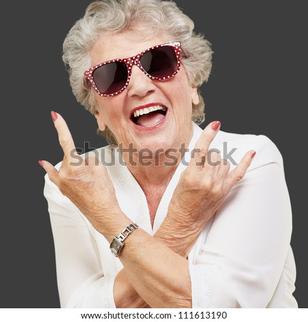 Senior woman wearing sunglasses doing funky action isolated on black background - stock photo