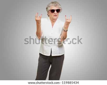 Senior woman wearing sunglasses doing funky action isolated on grey background - stock photo