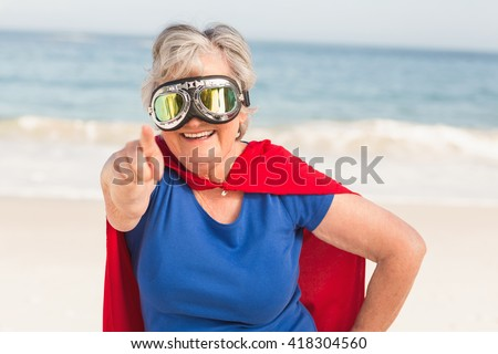 Senior woman wearing superwoman custome on a sunny day - stock photo
