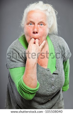 Senior woman whistling with her fingers. Acting young. Studio shot isolated on grey background. - stock photo