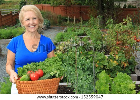 Senior woman with a basket of fresh vegetables. Also available in vertical.