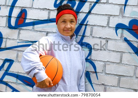 Senior woman with a basketball, graffiti background - stock photo