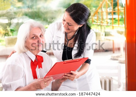 senior woman with a doctor looking at medical report - stock photo