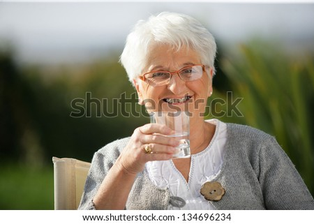 Senior woman with a glass of water - stock photo