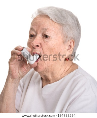 Senior woman with asthma inhaler on a white  background