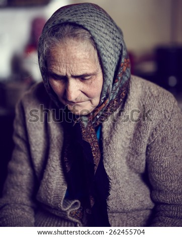 Senior woman with cardigan and kerchief indoor, deep in thoughts - stock photo