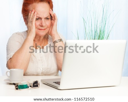 Senior woman with confused expression on her face sitting behind her laptop - stock photo