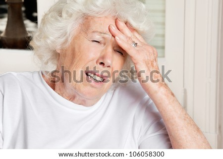 Senior woman with eyes closed suffering from headache - stock photo