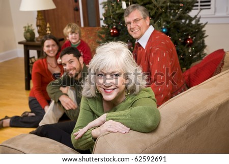Senior woman with family by Christmas tree - three generations