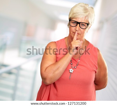 Senior Woman With Finger On Lips, Indoor - stock photo