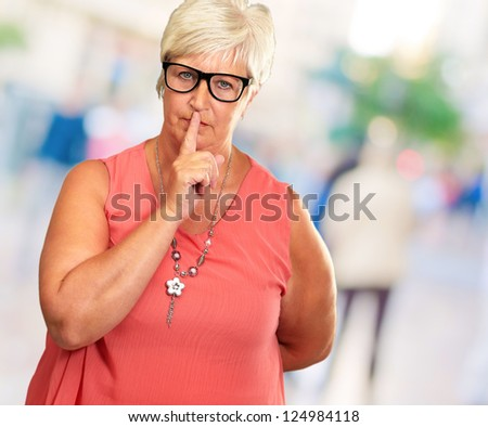 Senior Woman With Finger On Lips, Outdoor - stock photo