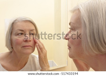 Senior woman with grey hair having a close look at the wrinkles of her facial skin in a mirror, thinking about aesthetic surgery