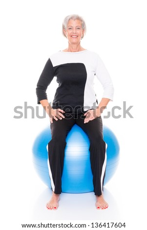 Senior woman with gymnastic ball in front of white backgound - stock photo