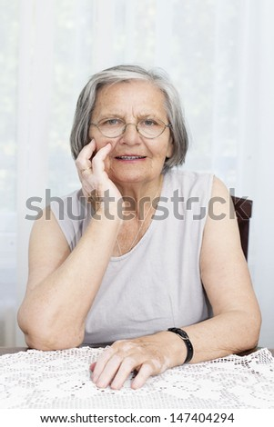 Senior woman with hand on her chin sitting at the table and looking at camera. - stock photo
