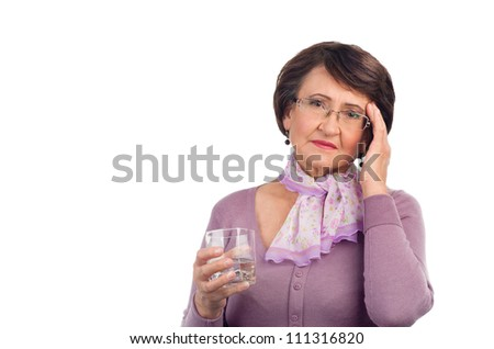 Senior woman with headache holding glass of water