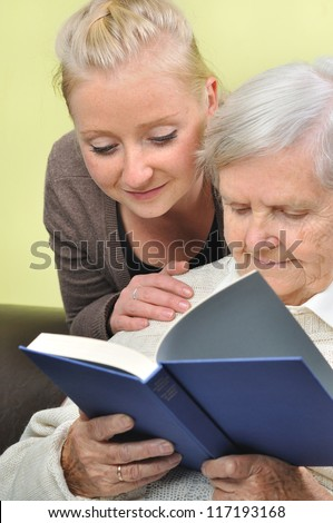 Senior woman with her caregiver in home reading book. MANY OTHER PHOTOS WITH THIS SENIOR MODEL IN MY PORTFOLIO. - stock photo