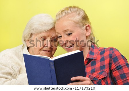Senior woman with her caregiver in home reading book. MANY OTHER PHOTOS WITH THIS SENIOR MODEL IN MY PORTFOLIO.