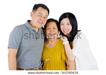 Senior woman with her daughter and son. Happy Asian family mother and adult offspring indoor portrait. - stock photo