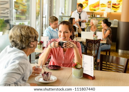 Senior woman with her daughter at cafe drinking eating happy - stock photo