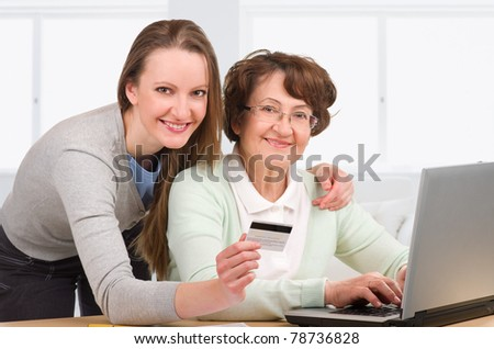 senior woman with her daughter online purchasing together - stock photo