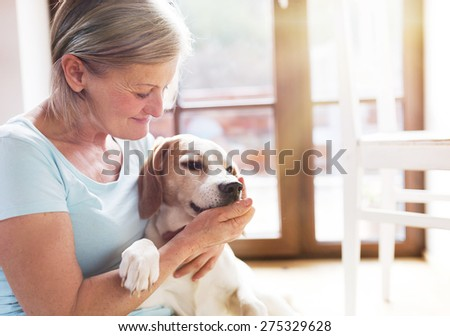 Senior woman with her dog inside of her house. - stock photo