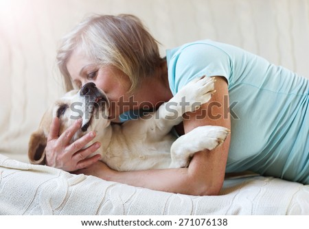 Senior woman with her dog on a couch inside of her house. - stock photo
