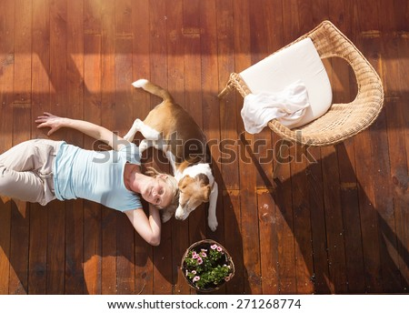 Senior woman with her dog on a terrace of her house. - stock photo