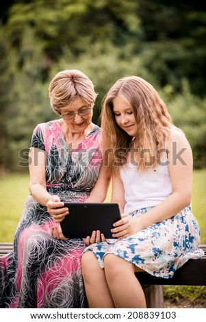 Senior woman with her granddaughter looking together on photos in smartphone - outdoor in nature