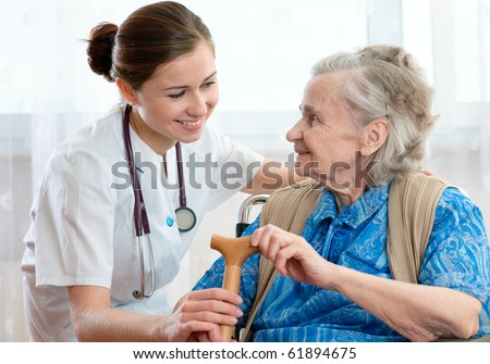 Senior woman with her home caregiver - stock photo