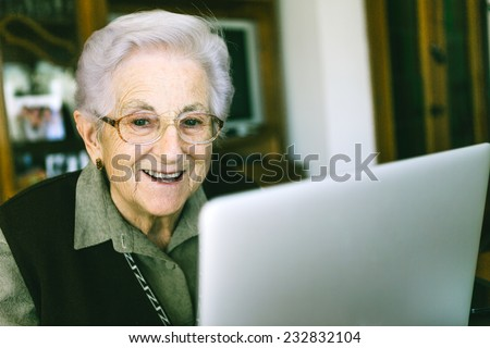 Senior woman with laptop at home - stock photo