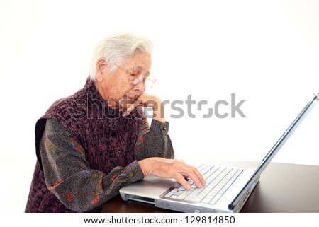 Senior woman with laptop at the desk - stock photo