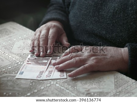 Senior woman with little euro money, toned image, colorized, selective focus, very shallow DOF
