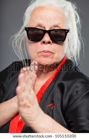 Senior woman with long grey hair wearing black and red kimono and black sunglasses. Doing karate moves. Studio shot isolated on grey background. - stock photo