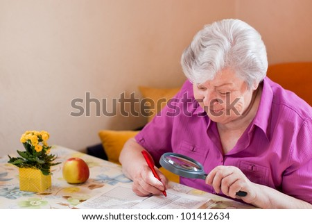 Senior Woman with magnifying glass  puzzled - stock photo