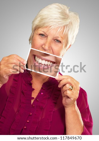 Senior Woman With Magnifying Glass Showing Teeth On Gray Background - stock photo