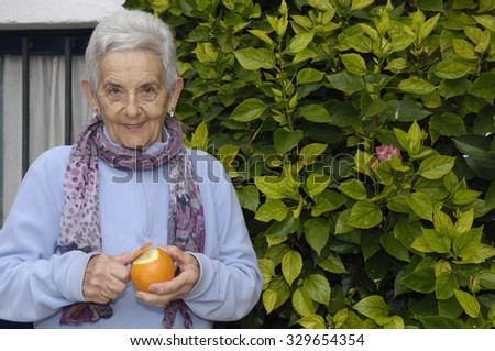 senior woman with orange fruit