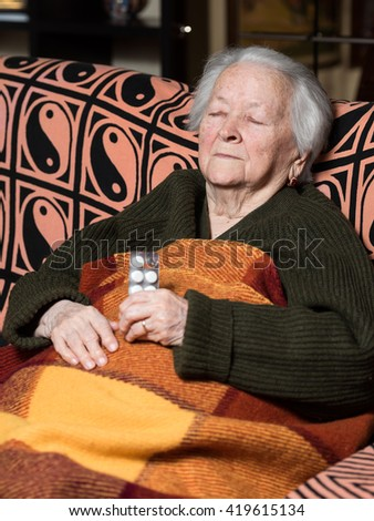 Senior woman with pills at home - stock photo