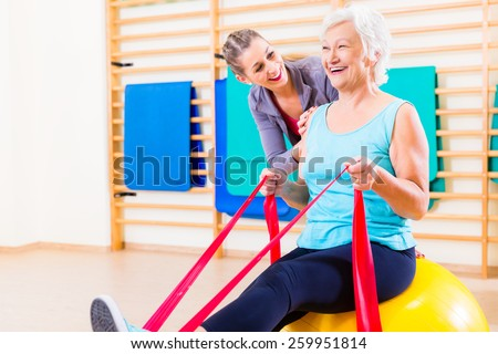 Senior woman with stretch band in fitness gym being coached by personal trainer - stock photo