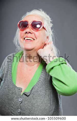 Senior woman with sunglasses deaf. Bad hearing. Hip and cool looking. Studio shot. Isolated on grey background. - stock photo