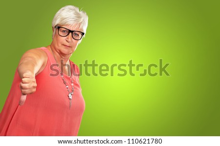 Senior Woman With Thumbs Down Isolated On Green Background - stock photo