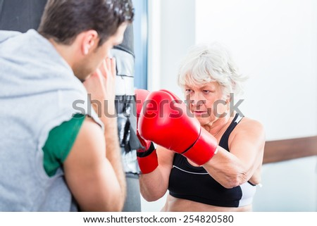 Senior woman with trainer in boxing sparring hitting sandbag - stock photo
