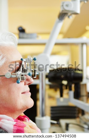 Senior Woman with trial frame gets examination at ophthalmologist - stock photo