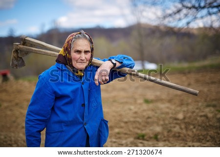 Senior woman with two hoes on her shoulder walking to a field - stock photo